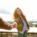 Attractive long hair woman pulling her boyfriends hand wishing to come along with her. Holding hand