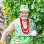uśmiechnięta kobieta w starszym wieku pouje do zdjęcia w ogrodzie różanym