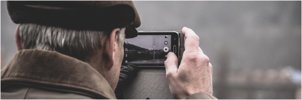 mężczyzna obrócony plecami do widza robi zdjęcie telefonem komórkowym