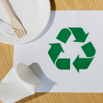 na stole kartka papieru ze znaczkiem recykling, plastikowy kubek, papierowa tacka i sztućce